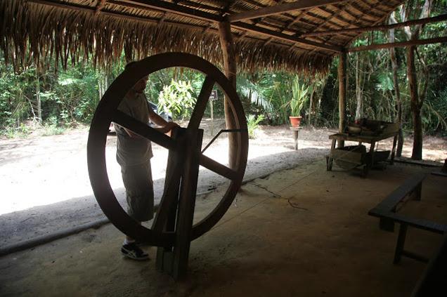 Bevor wir mit der Konstruktion der Maschinen für die Briquetteproduktion angefangen haben, haben wir uns erstmal in der Nähe nach lokalen Techniken umgesehen. Oben probiere ich eine traditionelle handbetriebene Vorrichtung zur Zerkleinerung von Maniok.