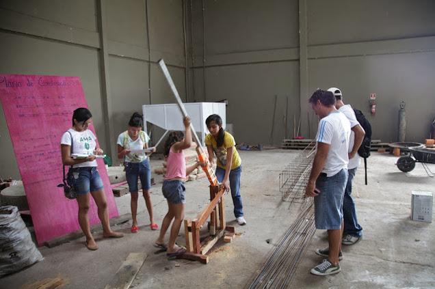 Schülerinnen von der benachbarten Schule probieren die Briquettepresse aus.